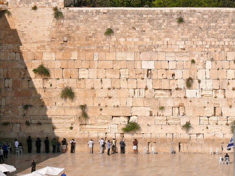 Visitors line up against the high stone wall in prayer.