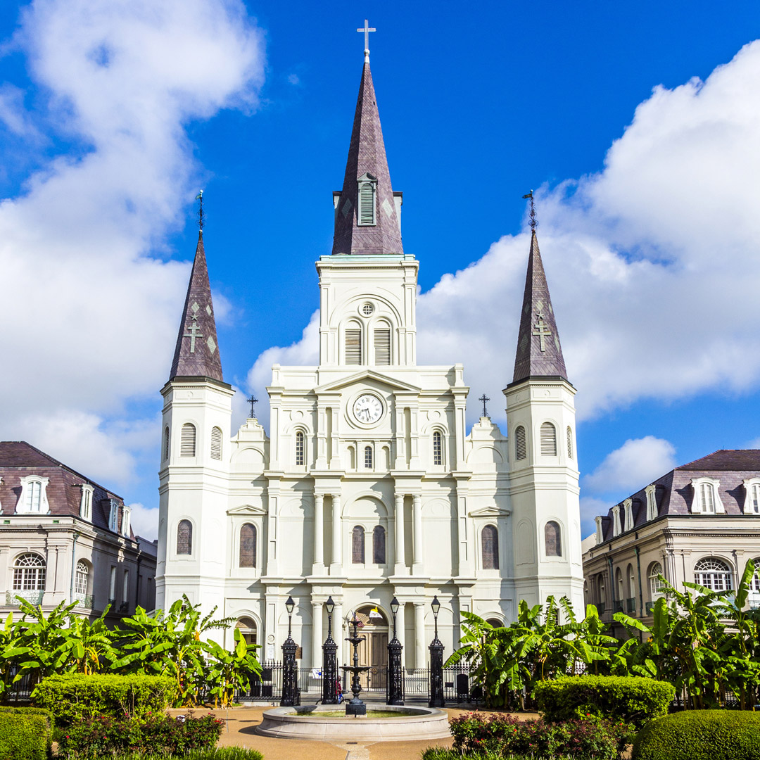 bright white St. Louis Cathedral in a well manicured park on a sunny day in New Orleans
