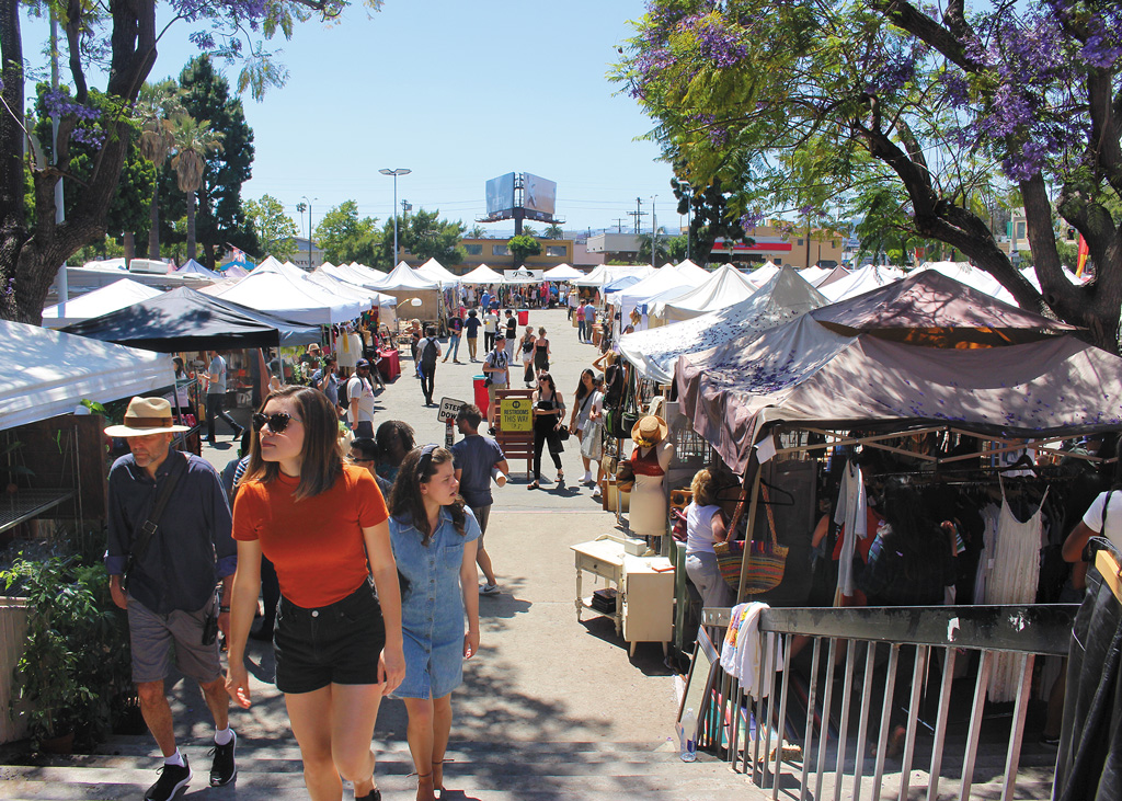 people walking between a line of commercial tents at an outdoor market in Los Angeles