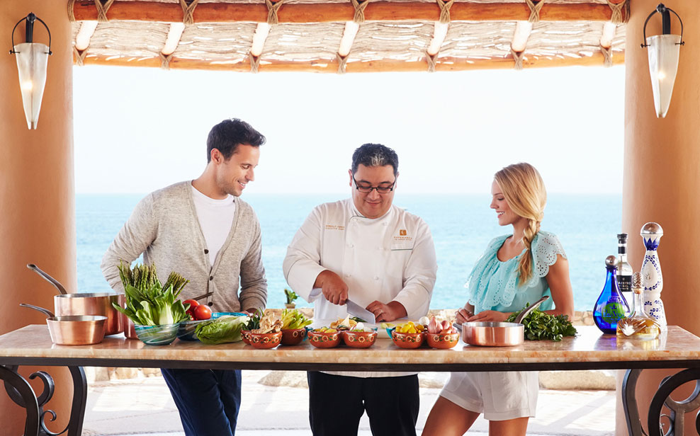 Chef Gonzalo Cerda demonstrates technique to two guests at an open-air butcher block.