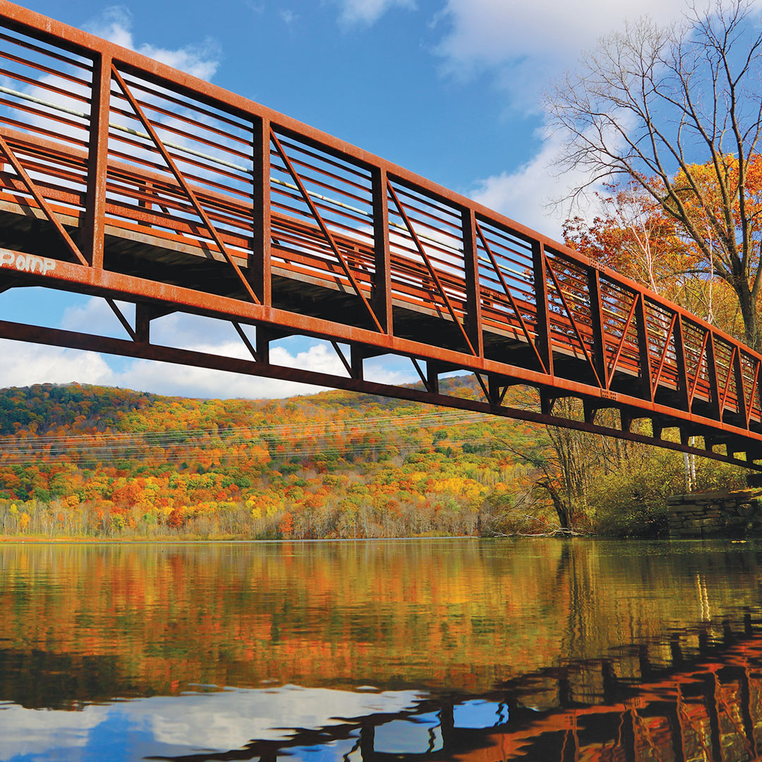 rusty bridge reflected in water backed by fall color