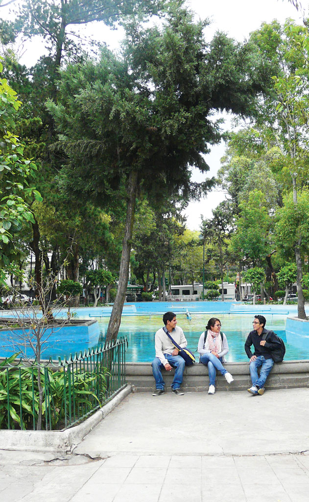 three people sitting on the edge of a fountain