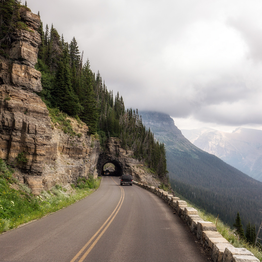 car approaching a tunnel through mountain on a cloudy day in Montana