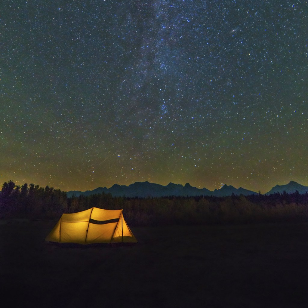 yellow tent lit up at night with stars above