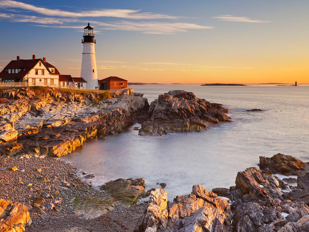 sunset on the rocky coast with a lighthouse