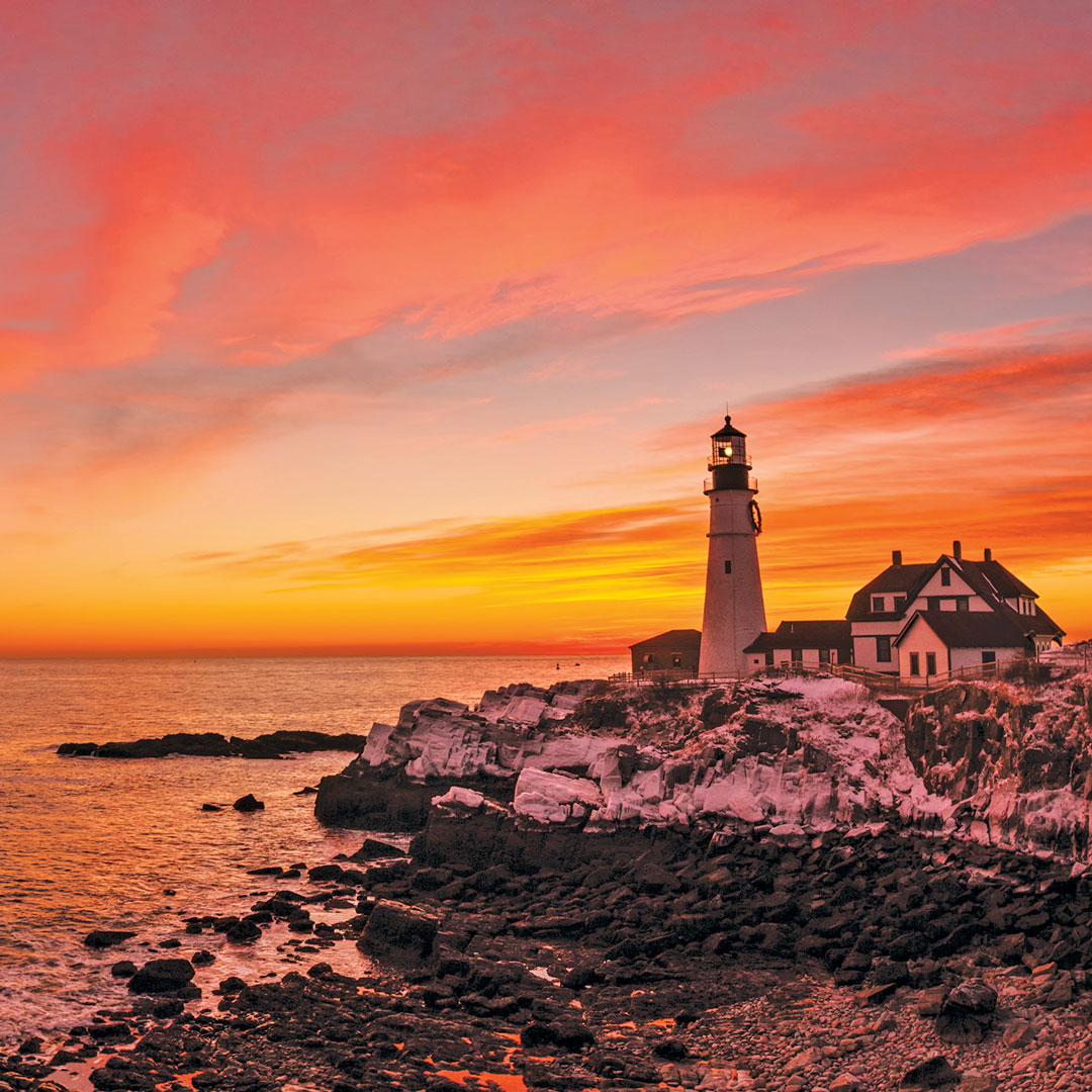 bright pink and orange sky behind Portland Head Lighthouse
