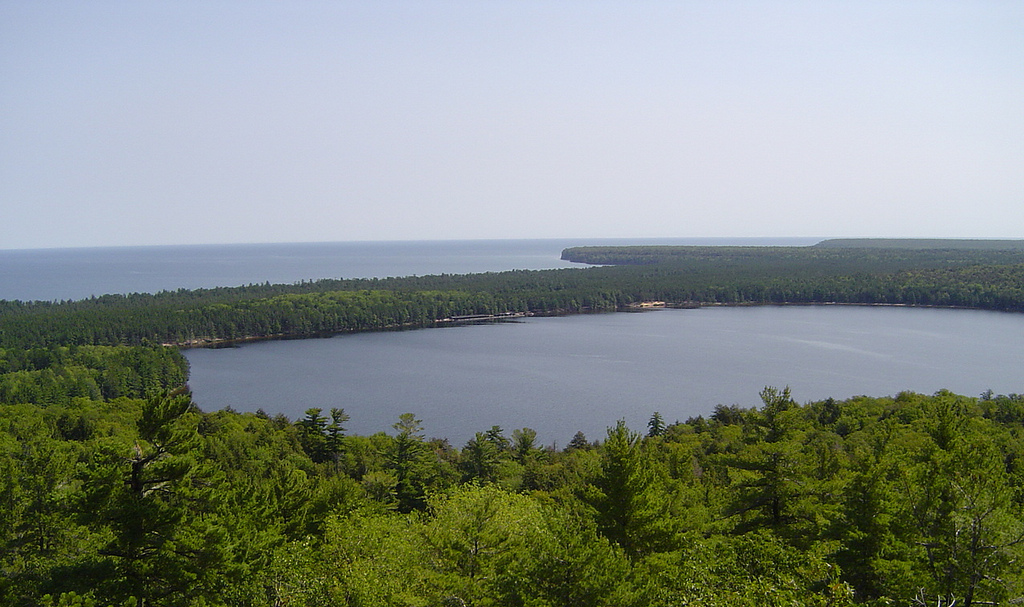 View down at Lake Superior and another lake across a sea of trees.