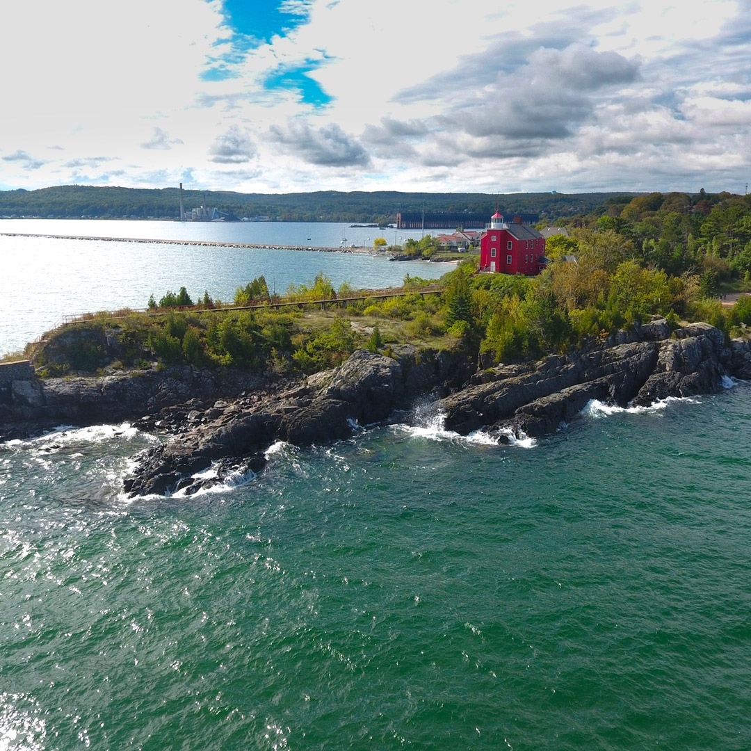 aerial view of a lighthouse on top of land jutting into lake superior