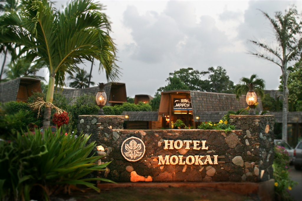 Nestled amongst lush tropical landscaping is the stone entrance sign of the Hotel Molokai.