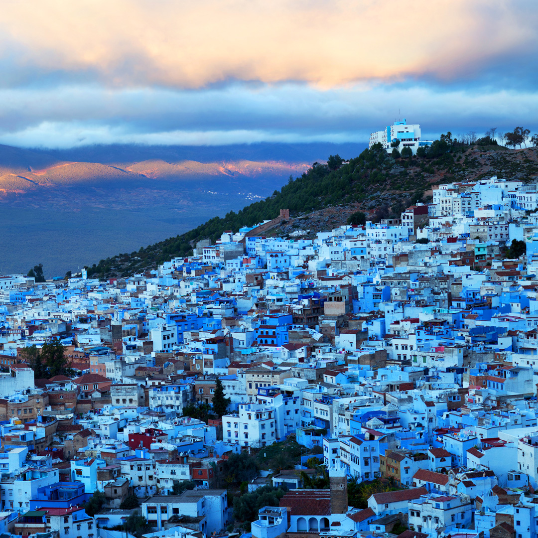 aerial view of Morocco's blue city of Chefchaouen with clouds overhead
