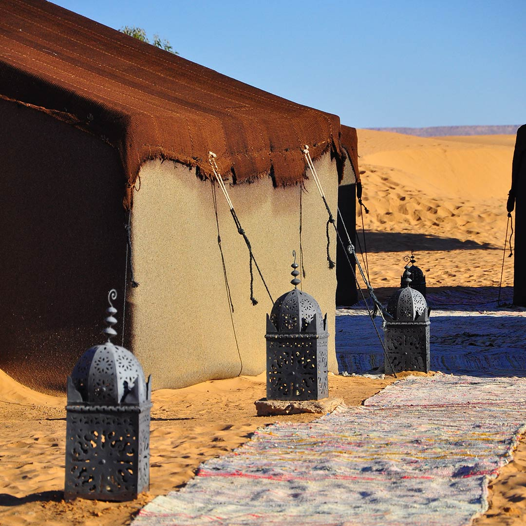 a path lined with lamps next to a desert tent in Morocco