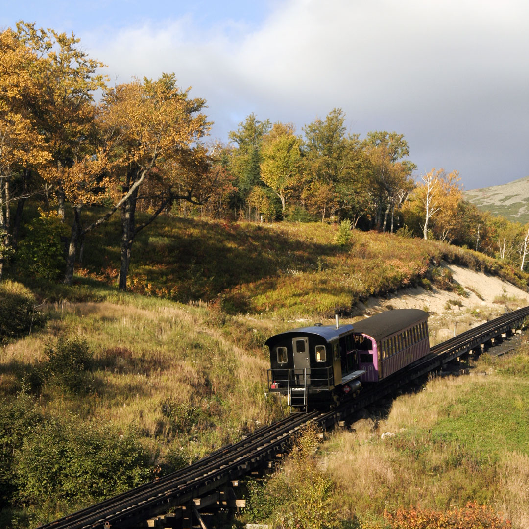 train chugging through fall color in New Hampshire