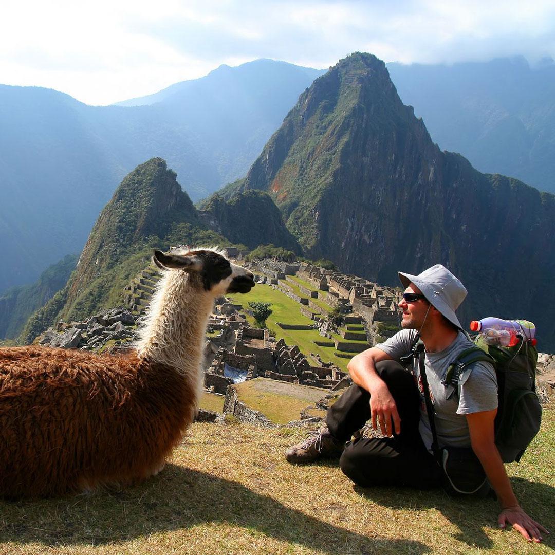 Machu Picchu Tourist sitting with Llama