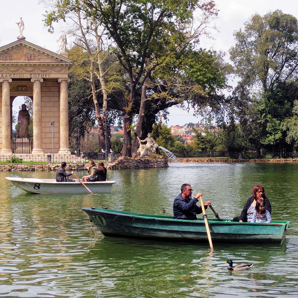A family in a small boat rows across a pond at Villa Borghese.