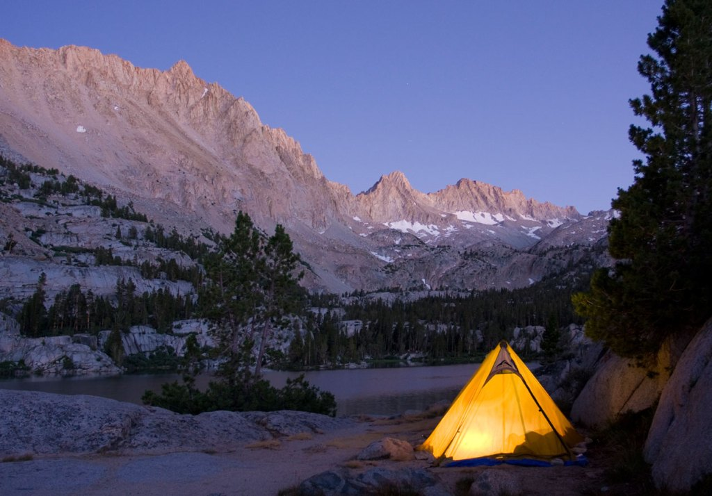 A personal tent glows warmly from within as dusk settles in the mountains.
