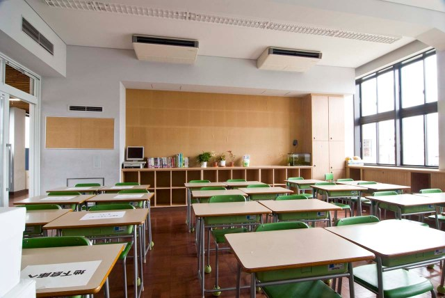 Neat rows of desks with green plastic chairs in a bright and airy classroom.