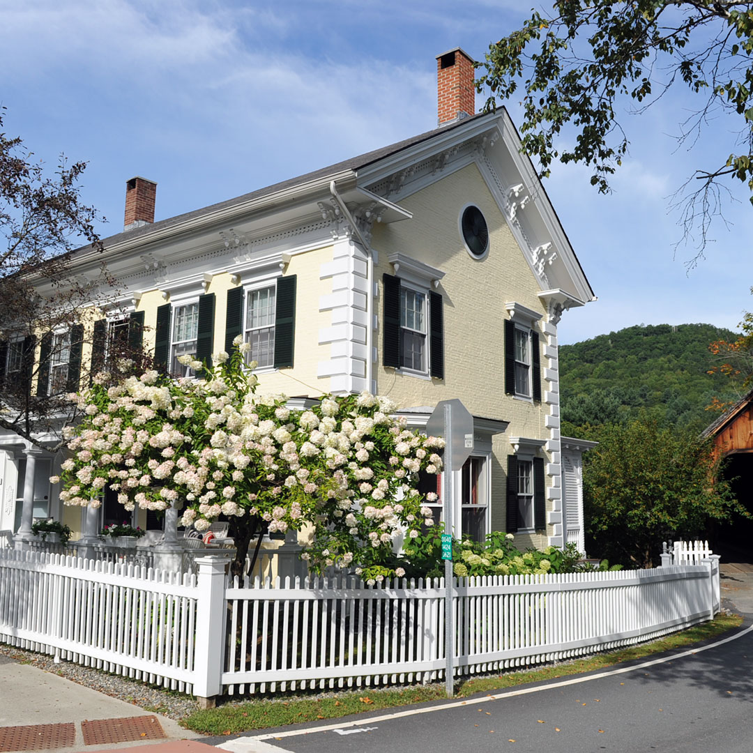 yellow New England house with roses and a picket fence in Woodstock Vermont
