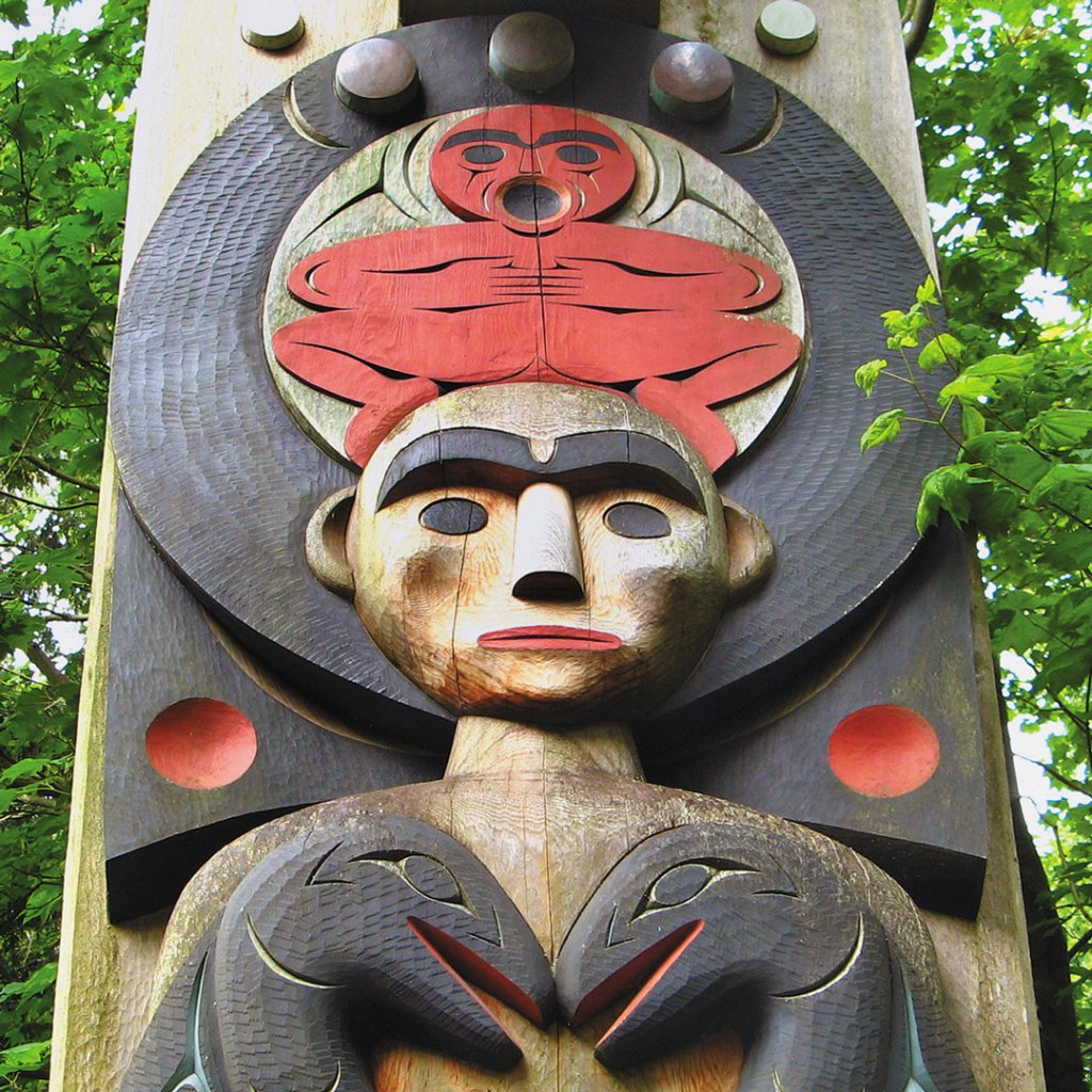 a face and two animals carved into a totem pole at the Museum of Anthropology in Vancouver
