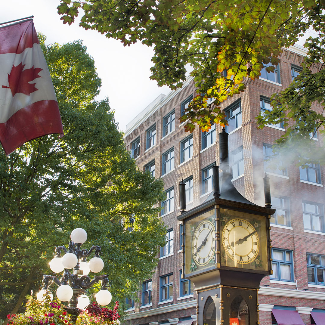 old clock spewing steam next to a Canadian flag in Vancouver