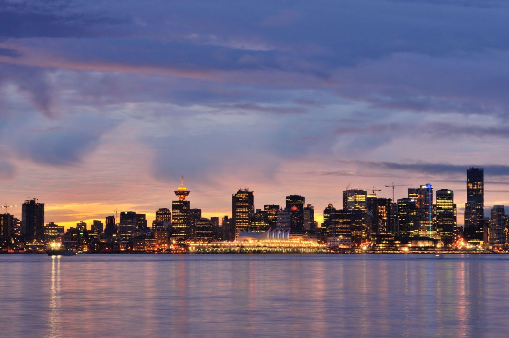 With the purple of dusk coloring the sky, Vancouver's city lights reflect in the water.