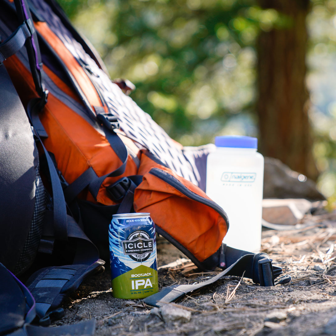 a can of beer propped up against a backpack