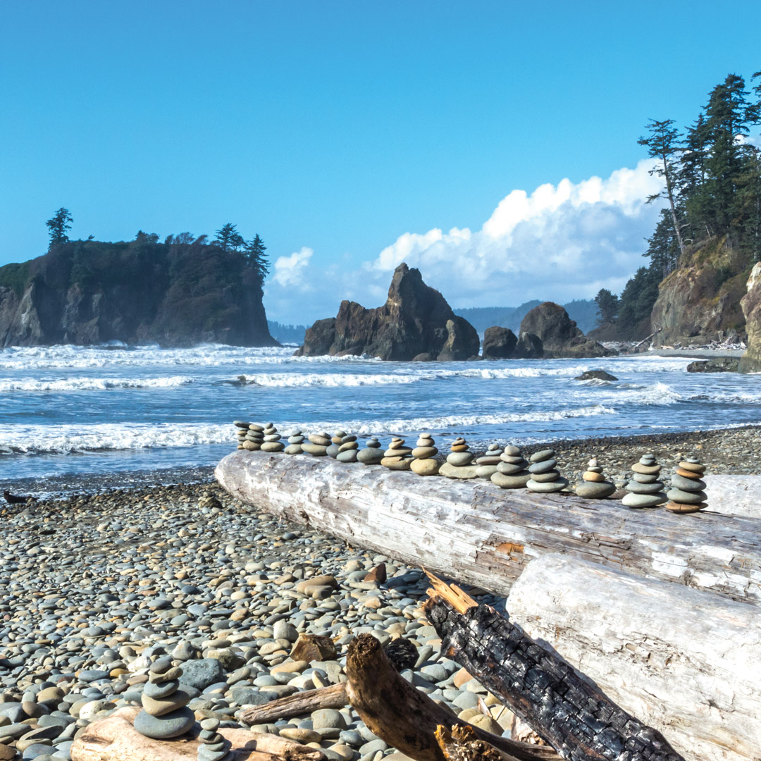 rocks stacked on a log at Ruby Beach