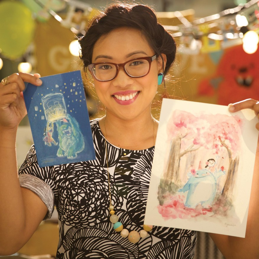 a woman in glasses holding up artwork