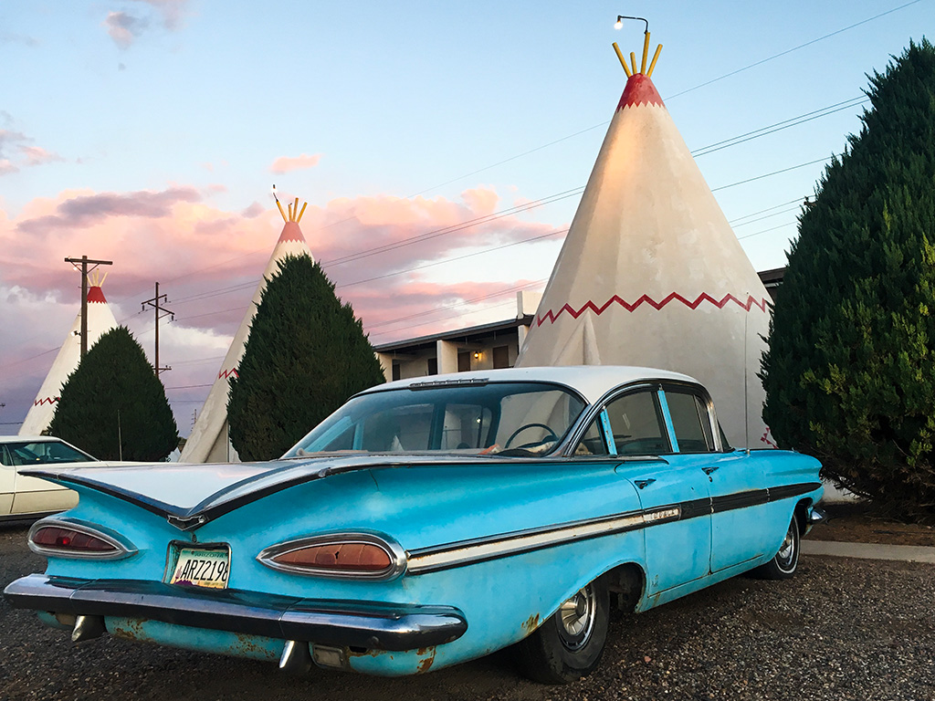A classic car in front of teepee shaped motel rooms at Holbrook.