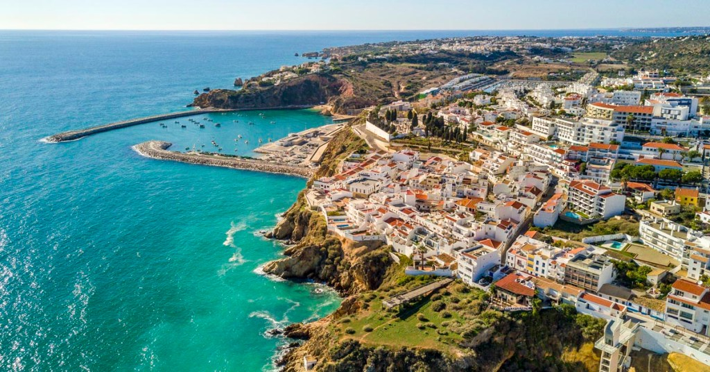 Aerial view of ocean, marina, buildings and cliffs in Albufeira, Algarve, Portugal.