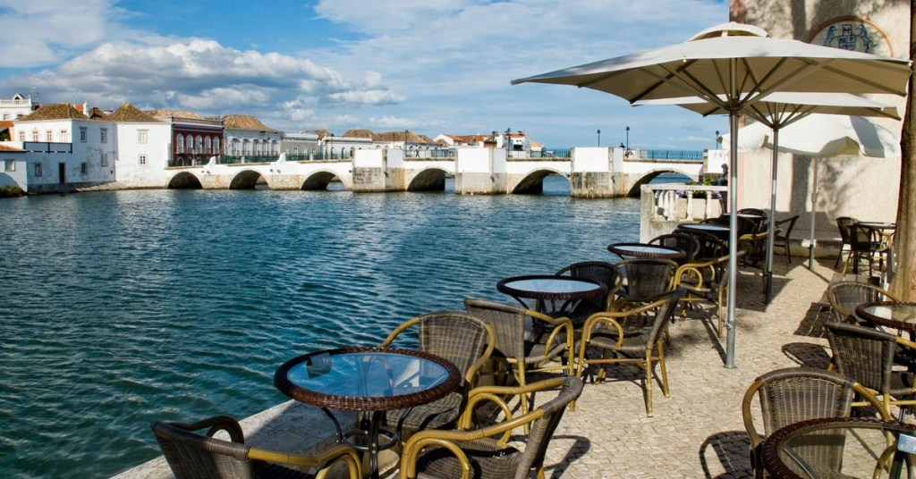 Roman bridge in the background, with cafe tables and umbrellas beside the Gilao river in Tavira, Algarve, Portugal.