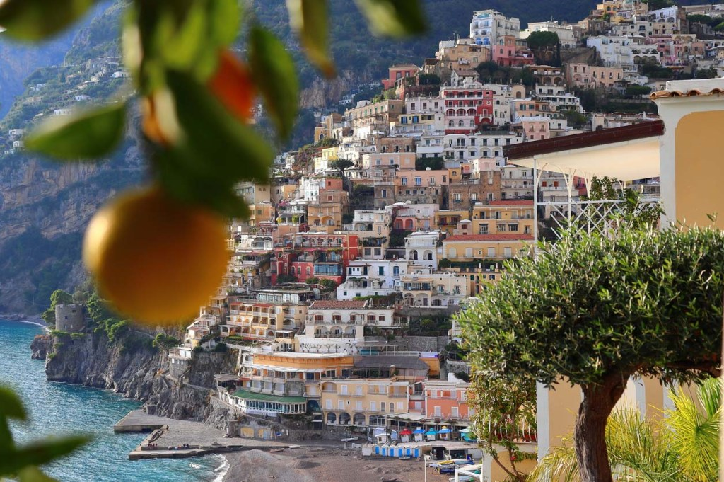 Lemon in the foreground of a view of the cliffside structures of Positano on the Amalfi Coast, Italy.