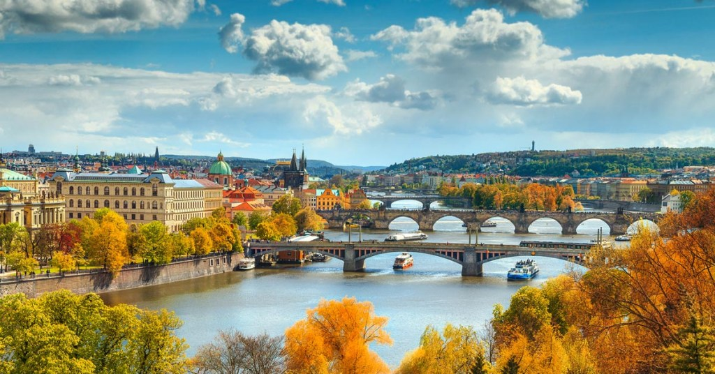 Autumn panorama of boats on the river and Prague city, Czech Republic, Europe.