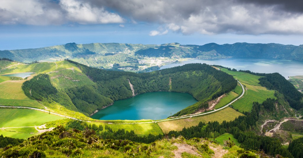 teal colored lake in a volcanic crater surrounded by green mountainous terrain