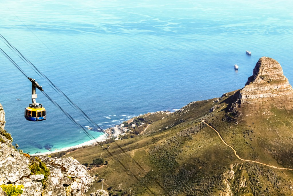 Top down view from Table Mountain of a cable car and the Lion's Head on the right and Atlantic Ocean in the background