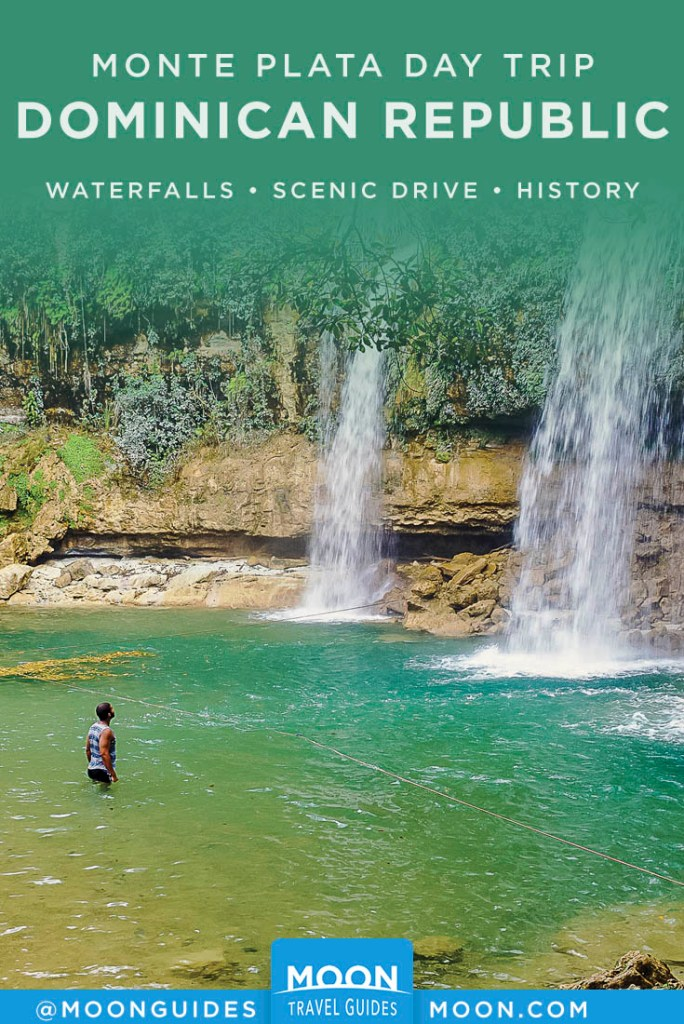 Man wading in water, looking up at two waterfalls. Pinterest graphic.