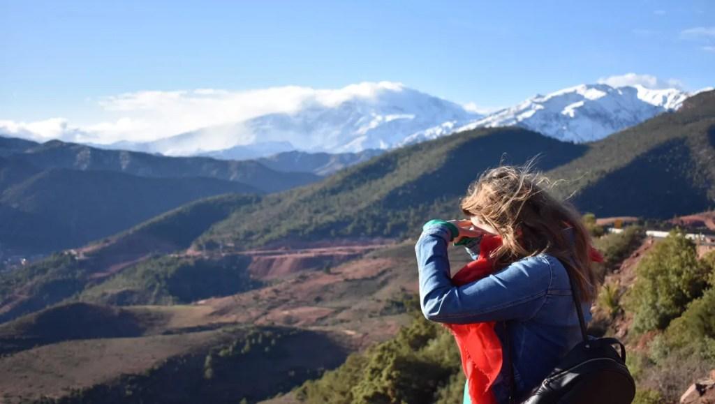 woman looking through binoculars at the mountainous landscape