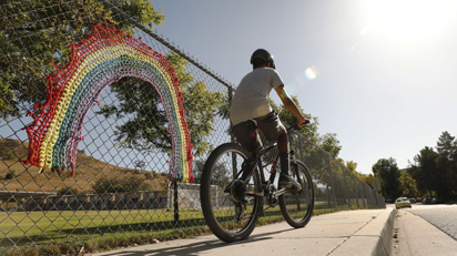 Image of boy riding bicycle near fence with crocheted rainbow