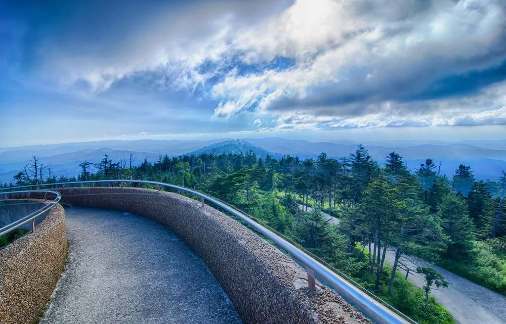 concrete walkway overlooking forested mountains
