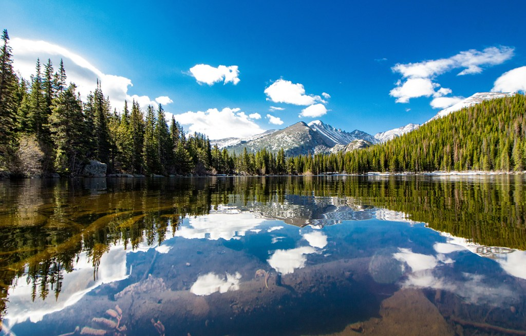 reflection of trees, mountain and clouds in a glassy lake surface