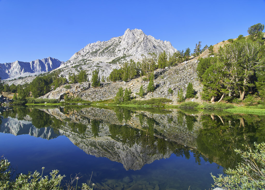 Photo of Long Lake and Bishop Pass with mountains, trees, and clear blue water