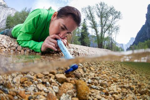 hiker using a lifestraw to drink water from a stream