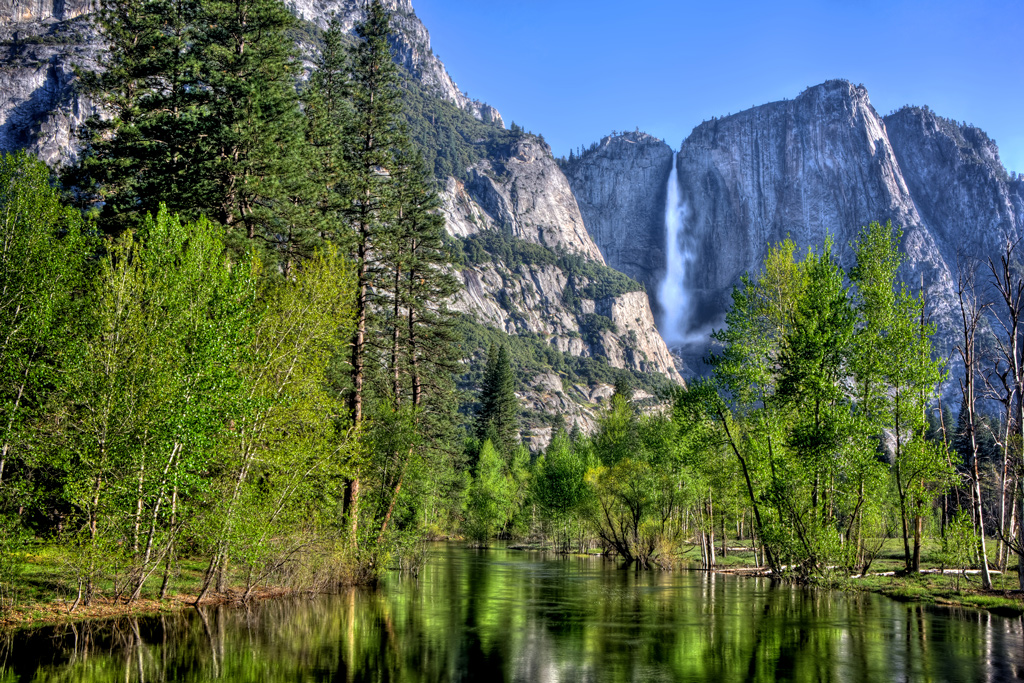 the main stream at Yosemite Falls in Yosemite National Park with a reflective Merced River in the foreground.