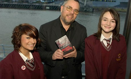 Alan Gibbons with pupils and one of his youth novels