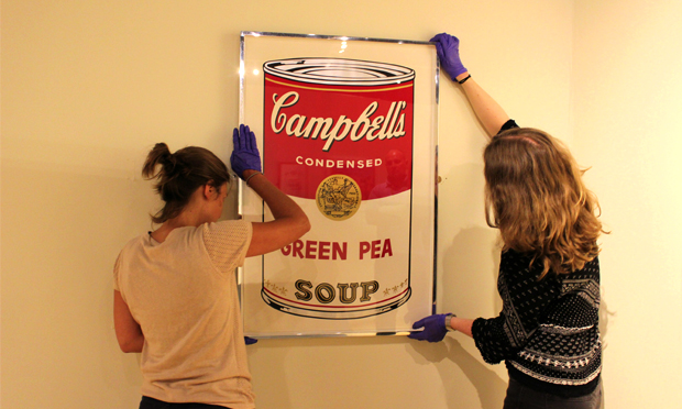 Soup of the day: Hackney Museum workers hang their Warhol. Photograph: Hackney Museum