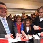 Dr. Andreas Beyer (l.) und Alexander Flieger (r.) zerschnitten mit Schülern das Band zum Eingang des Schülerladens.