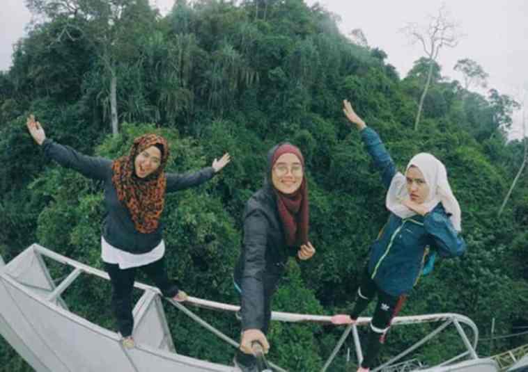 Demi foto selfie yang berbeda, tiga gadis ini nekat panjat papan reklame