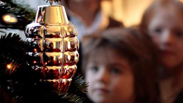 Silverfärgad handgranat i julgran mend tindrande barn