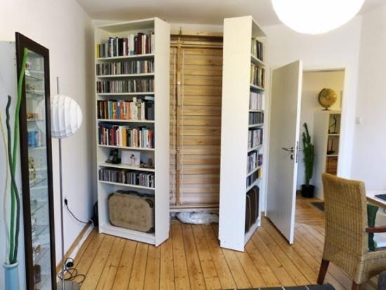Säng som är inbyggd bakom bokhyllor och kan fällas ned när hyllorna viks ut