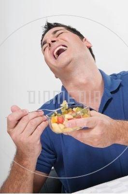 Skrattande man äter fruktsallad