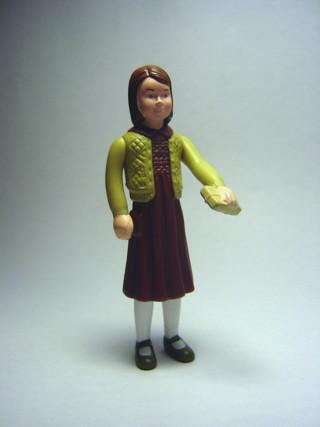 plastfigur med höjd vänsterarm med bok i